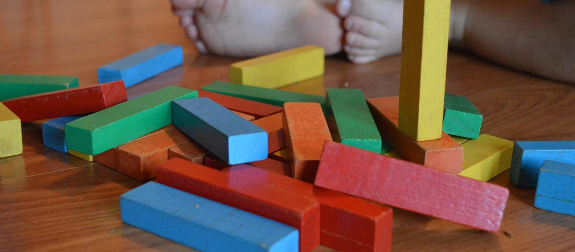 Träklossar i olika färger samt och barnfötter i bakgrunden.